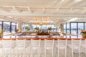 Indoor event space bar with stools overlooking marina